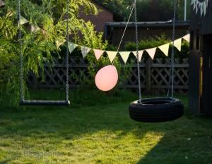 Schaukel mit Sitz und Reifen, Wimpelkette und rosa Ballon