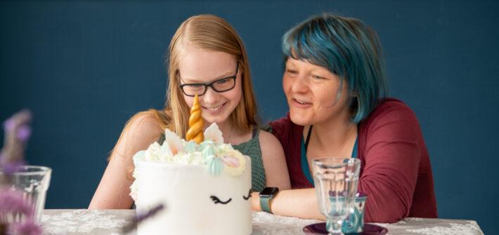 Mutter und Tochter freuen sich über Einhorntorte