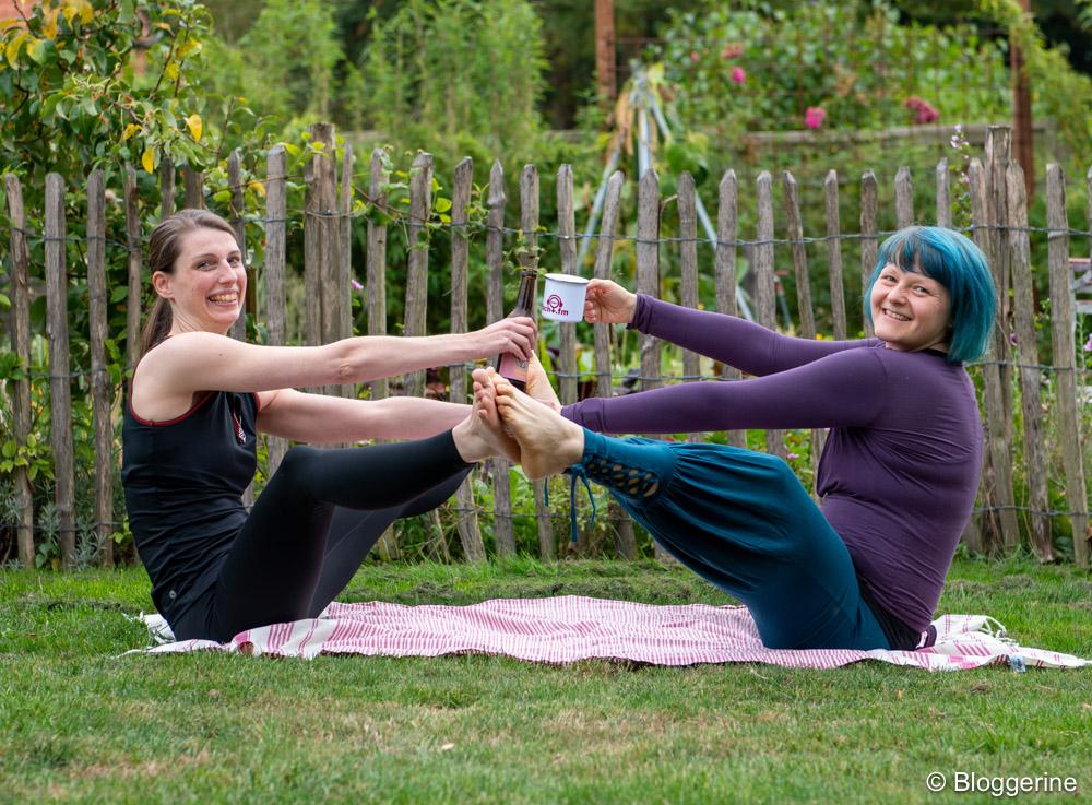 Bloggerine und Dr. Macht in Yoga-Partnerpose Boot und prosten sich mit Bier und Tee zu
