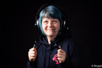 Aline mit Kopfhörern und Mikro vor schwarzem Hintergrund