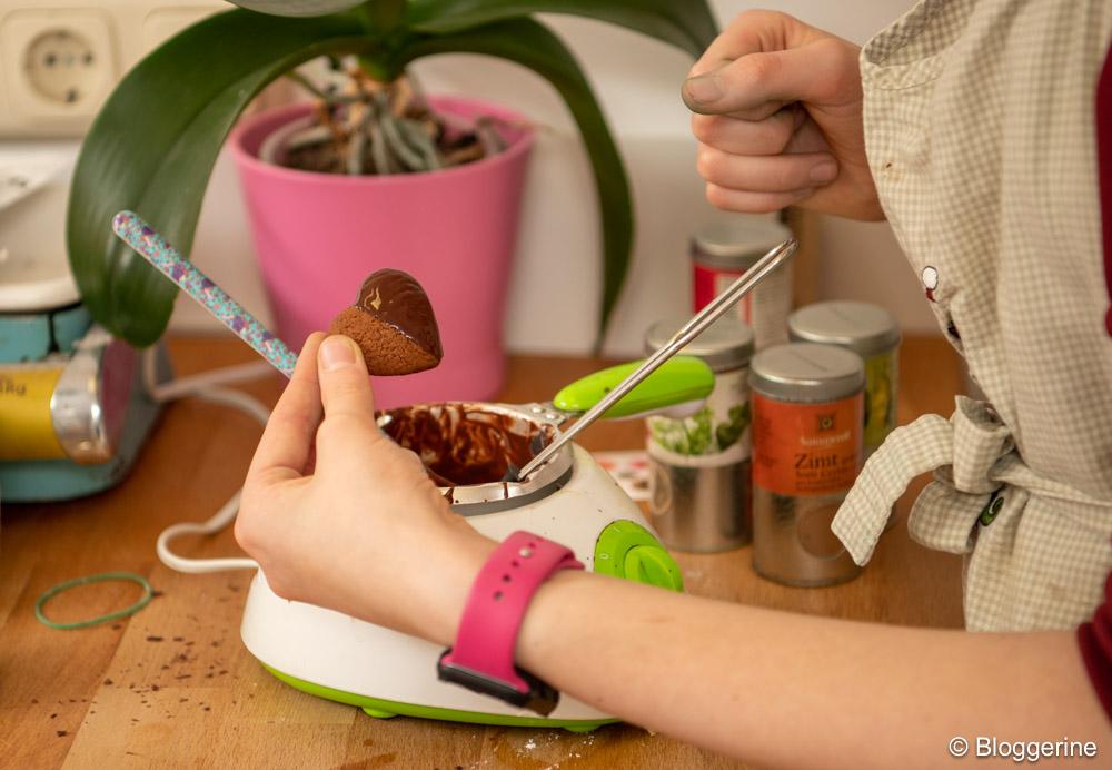 Mädchen hält Lebkuchenherz mit Schokolade über Schokoschmelzer