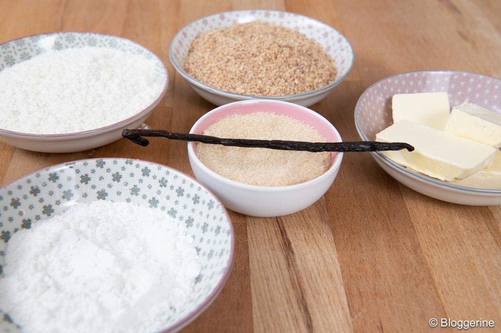 Schüsseln mit Mehl, Puderzucker, Zucker, Mandeln, Butter und Vanilleschote
