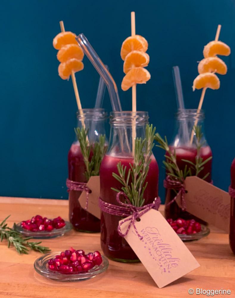 roter Drink in kleinen Flaschen mit Mandarinen an Spieß