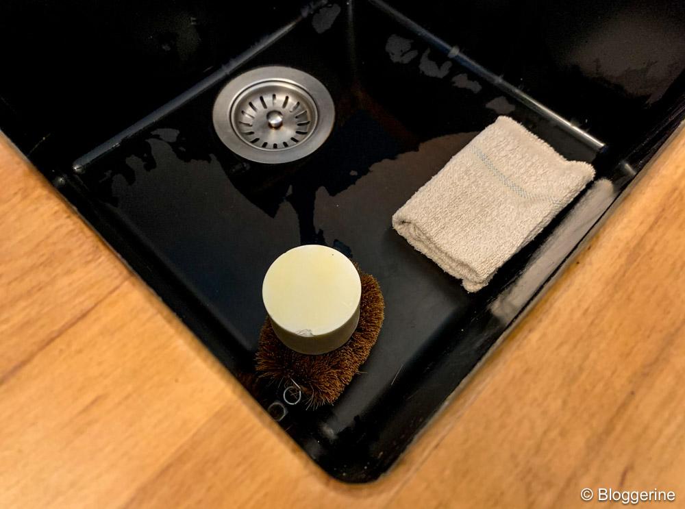 runde Seife auf Seifenigel und Spüllappen in schwarzem Spülbecken